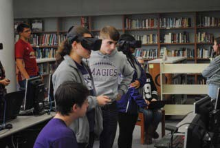 One of Kaser's STEM VR students assists a pair students in the health class.  Both students go through the experience, with the student in the headset relaying information to the person taking notes on a computer.