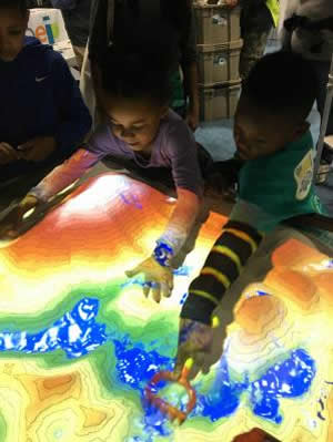 The ARsandbox combines an actual sandbox with a 3D camera, a  digital projector and a computer to display a topographic map that adjusts as  sand is moved around inside the box.