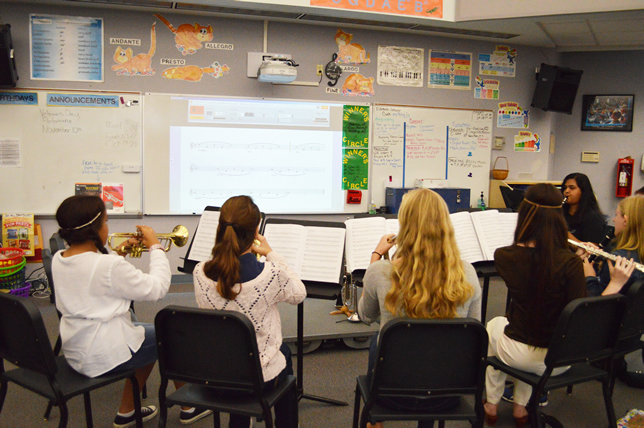 Music teachers at Oak View Middle School use an interactive projector to display a score, and students use an app that tells them if they are sharp or flat.